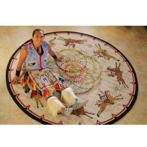 Native American sitting on a tan round area rug