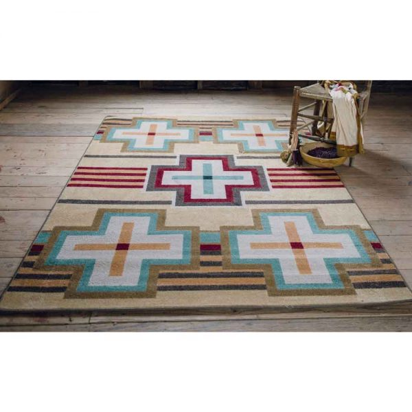 Pale yellow and turquoise rug with Southwest cross on wood floor