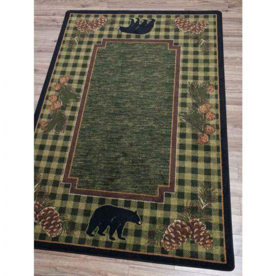 Green area rug with plaid border and bears and pine cones