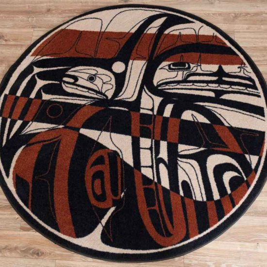 Round rug with a native print in brown and black on a tan background