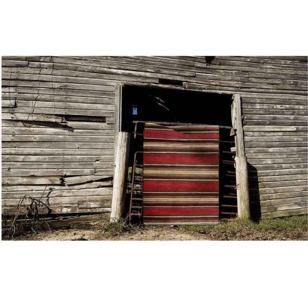 Red and brown striped Southwestern rug hanging on barn
