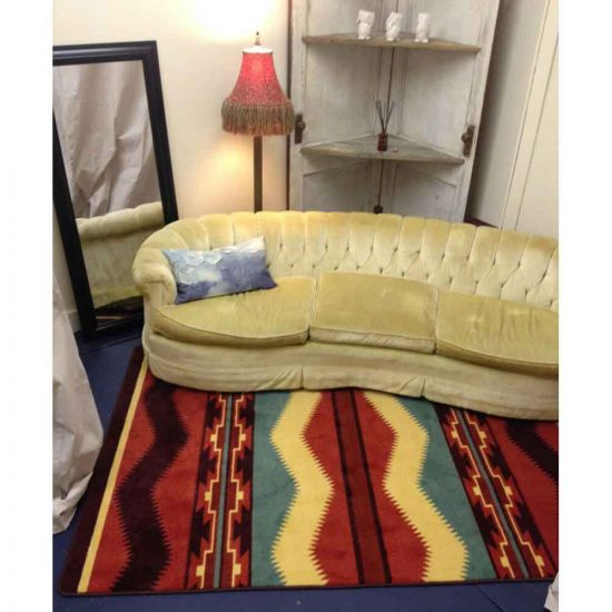 Red, yellow, and green Southwest rug with yellow velvet sofa