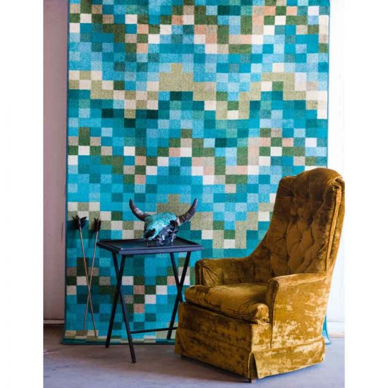 Yellow velvet chair in front of turquoise print rug
