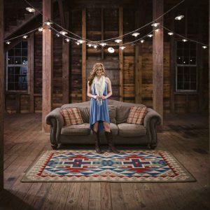 Rustic room scene with woman standing on multicolor Southwestern print area rug