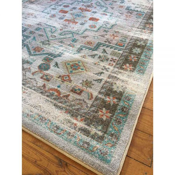 Corner shot of a turquoise and tan area rug with a distressed Persian design