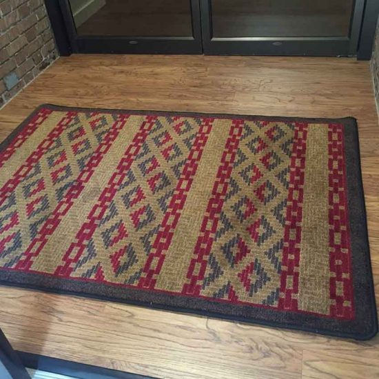 Area rug with a geometric tribal pattern in red and brown