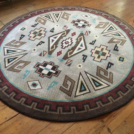 Round Southwestern rug with gray, brown and accent of turquoise