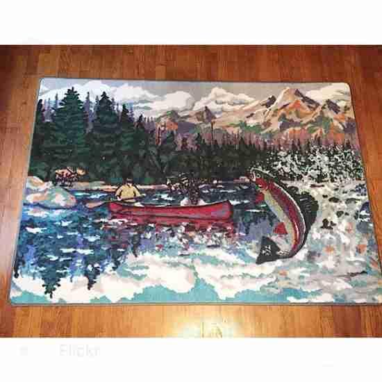 Rustic area rug with a mountain lake fishing scene