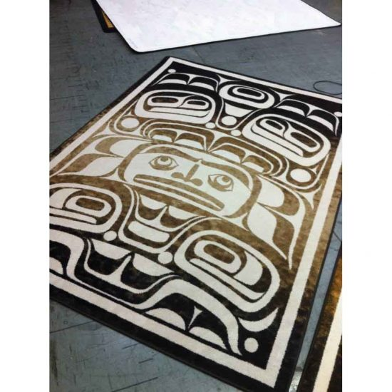 Tan and black rectangle area rug with Native mask prints