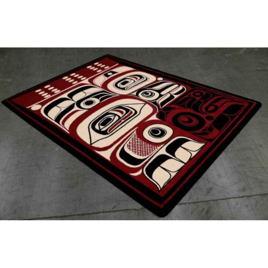 Area rug with Native masks designs in red, black, and tan