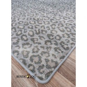Corner of rug with leopard print in black and tan leopard print on a gray background