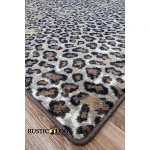 Closeup of the corner of an area rug with leopard print in brown, grey, and black