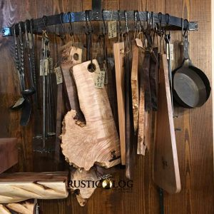 Cutting boards and hand-forged utensils hanging on a pot rack