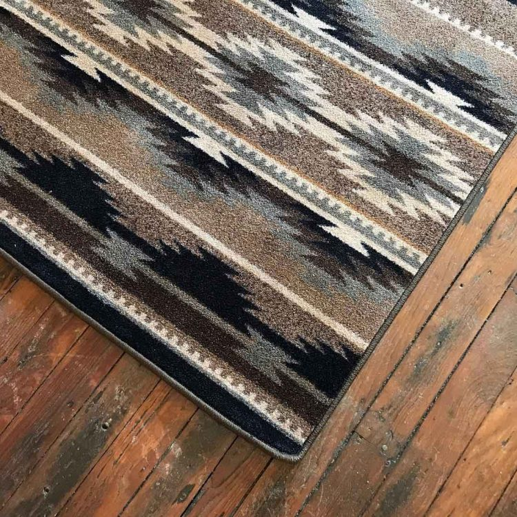 Close up of a neutral Southwestern area rug to show color and details of print