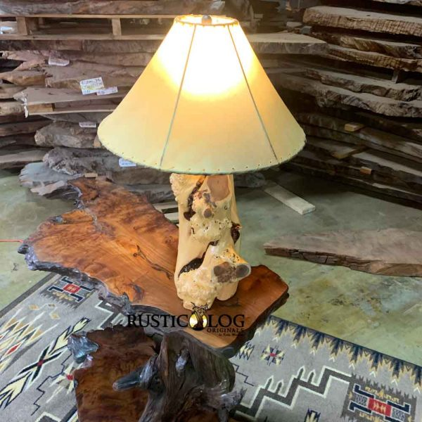 Log table lamp with rawhide shade on a live edge console