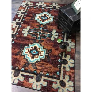 Rust colored area rug with native patterns in tan and turquoise