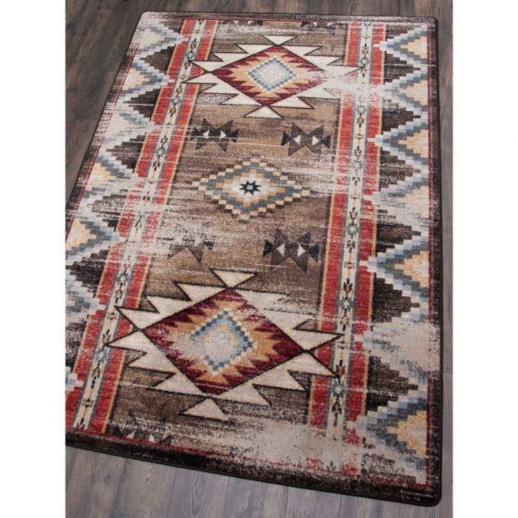 Distressed brown area rug with tan, red, and blue Southwestern prints