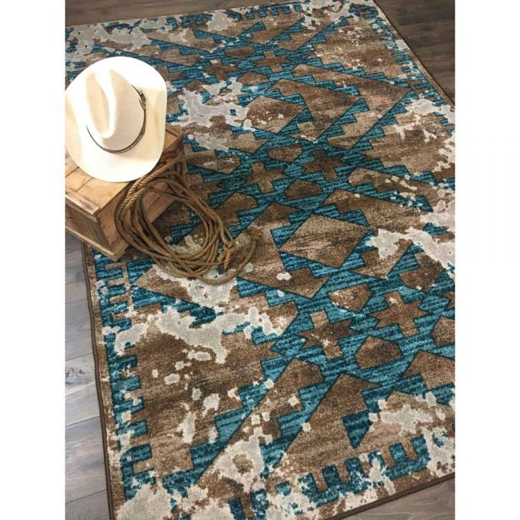 Southwestern area rug with a distressed turquoise pattern on a taupe background
