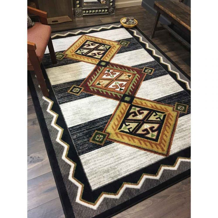 Area rug with orange and red Southwestern designs on a color block black and white background
